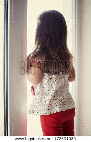 Child girl looking out the window and waiting for somebody