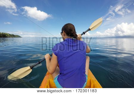Young woman in a kayak kayaking in a tropical resort on Vanua Levu Island Fiji. Real people copy space