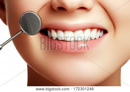 Woman's Smile. Healthy White Woman's Teeth And A Dentist Mouth Mirror Closeup. Dental Hygiene, Oral