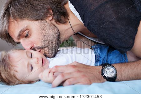 A young handsome father is kissing his adorable baby.