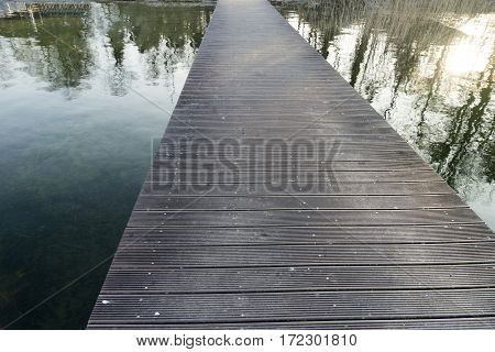 Infinity long pedestrian bridge over a lake with reflections