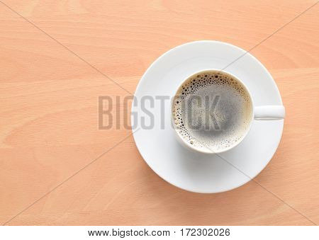 Cup of coffee on white plate on the table