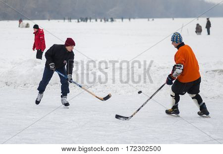 DNEPROPETROVSK UKRAINE - FEBRUARY 08, 2014: Amateur pair (young and mature men) playing hockey on a frozen river Dnepr in Ukraine at February 08, 2014