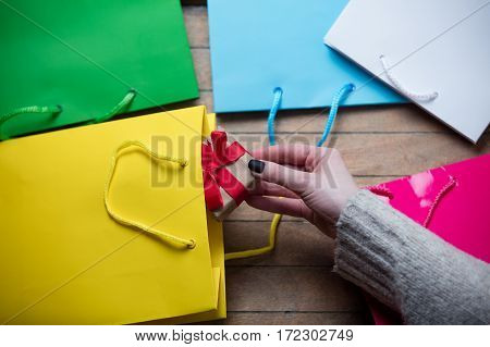 beautiful woman hands holding cute gift and putting it inside one of the shopping bags on the wonderful colorful shopping background