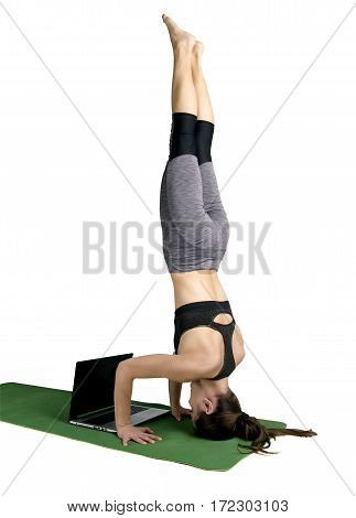Athletic Young Woman Doing Yoga. Headstand With A Laptop Isolated On White Background In Studio