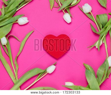 beautiful red heart shaped toy and tender white tulips lying on the wonderful pink background