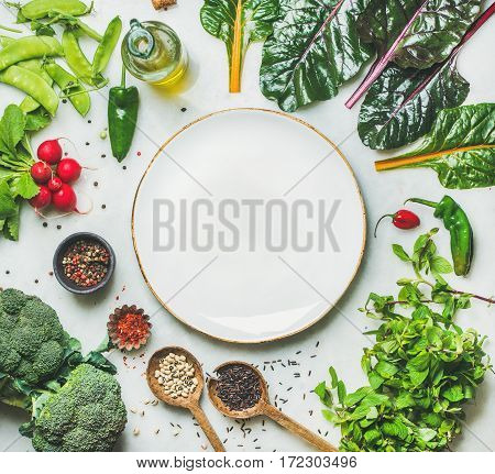 Fresh raw greens, vegetables and grains over light grey marble kitchen countertop, wtite plate in center, top view, copy space. Healthy, clean eating, vegan, detox, dieting food concept