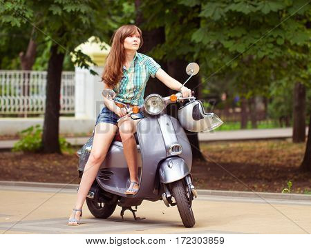 Young Woman Poses Near The Scooter In City Park. Summer Time