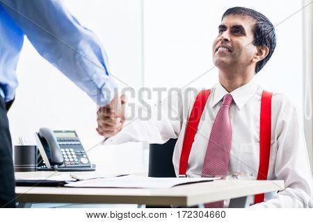 Asian business partners after reaching agreement shaking hands in office sealing the deal