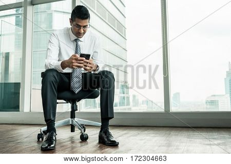Indian businessman using a mobile phone while sitting down in a modern office