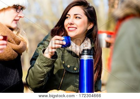 Young female friends talking while drinking a hot beverage outdoors in a winter day