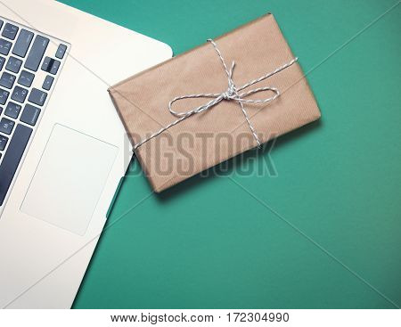 beautiful small gift and modern silver laptop on the wonderful blue background