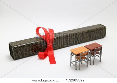 Study desks and diploma with a red ribbon on white background. Graduation concept.