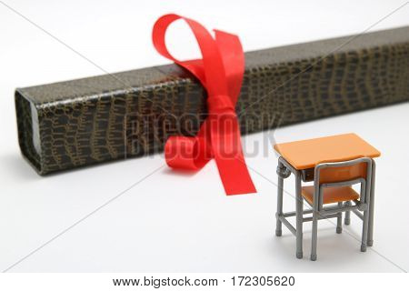 Study desk and diploma with a red ribbon on white background. Graduation concept.