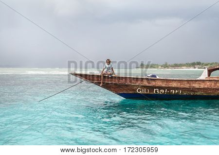 Gili Trawangan, Indonesia - 26 January 2017: smiling man in sunglasses sits on the boat in the sea on the background of the cloudy sky and blurry shore. Editorial photo. Horizontal.
