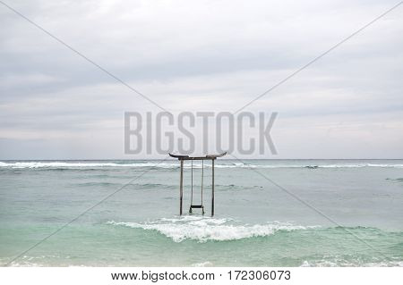 Gili Trawangan, Indonesia - 28 January 2017: wooden swing stands in the water of the sea on the cloudy sky background. There are waves on the sea surface. Editorial photo. Horizontal.