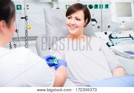 Nurse in hospital checking access at woman blood donor