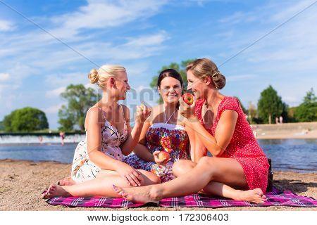 Woman eating fruit at river beach picnic