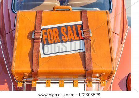 For sale sign stick on brown traveling leather bag carry behind the brown retro car exclusive and retro automobile trading.