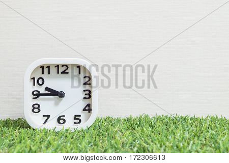 Closeup white clock for decorate show a quarter to ten or 9:45 a.m. on green artificial grass floor and cream wallpaper textured background with copy space