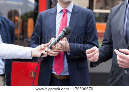 Female journalist or reporter holding microphone conducting media interview