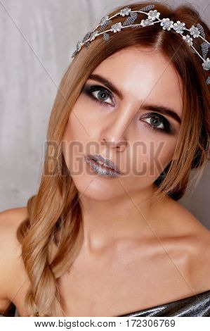 Beautiful girl model in the Studio shooting beauty. Silver makeup, hair in a sloppy spit, silver top.
