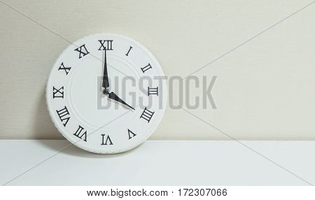 Closeup white clock for decorate show 4 o'clock on white wood desk and cream wallpaper textured background with copy space