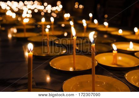 Close up of Candles in white plates.
