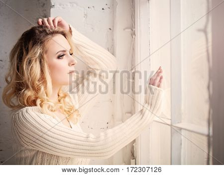 Blonde Woman Looks out the Window and Worries