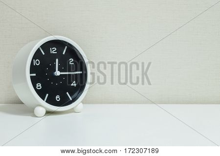Closeup black and white alarm clock for decorate show a quarter past twelve or 12:15 a.m.on white wood desk and cream wallpaper textured background with copy space