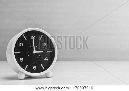 Closeup alarm clock for decorate in 3 o'clock on wood desk and wall textured background in black and white tone with copy space