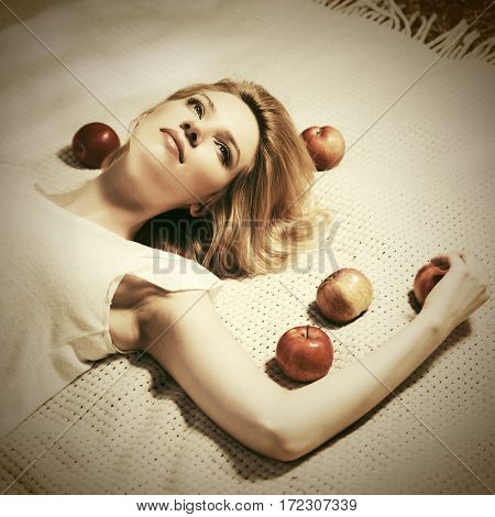 Happy young woman with apples lying on the plaid. Stylish fashion model outdoor