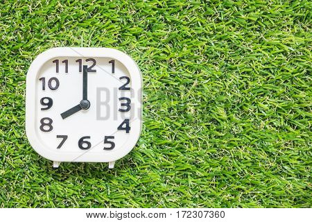 Closeup white clock for decorate in 8 o'clock on green artificial grass floor textured background with copy space