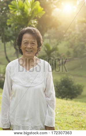 Portrait of healthy Asian senior woman walking at outdoor nature park, morning beautiful sunlight background.