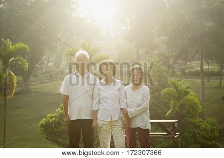 Portrait of healthy Asian seniors group enjoy retired life at outdoor nature park, in morning beautiful sunlight at background.
