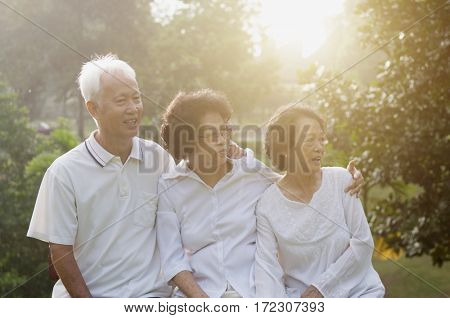 Portrait of healthy Asian seniors group at outdoor nature park, in morning beautiful sunlight at background.