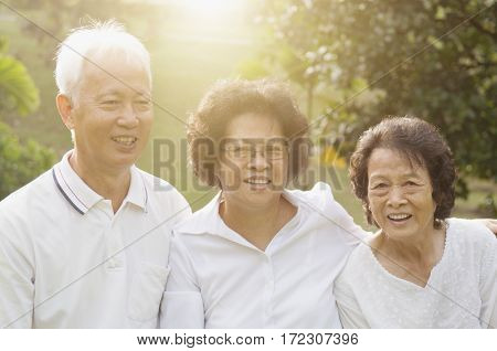 Group of healthy Asian seniors having fun at outdoor nature park, in morning beautiful sunlight at background.