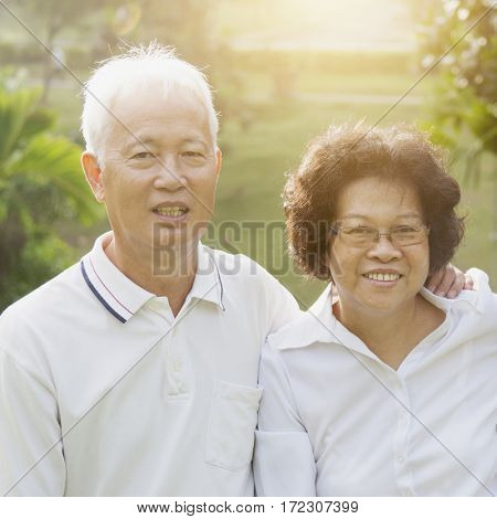 Portrait of healthy Asian seniors retiree couple having fun at outdoor nature park, morning beautiful sunlight background.
