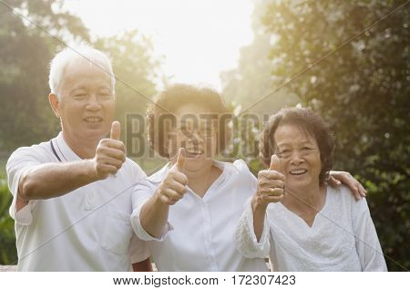 Group of healthy Asian seniors retiree giving thumbs up at outdoor nature park, in morning beautiful sunlight at background.