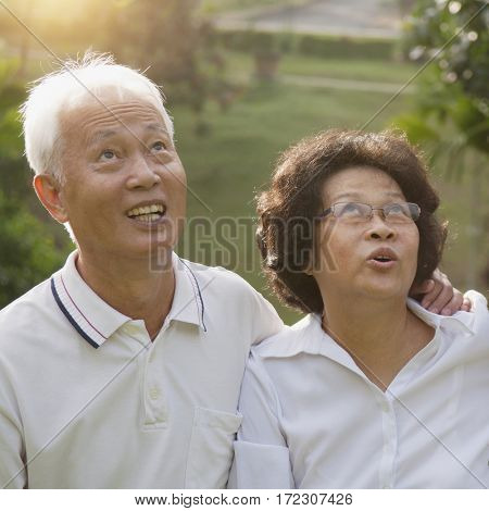 Portrait of healthy Asian seniors retiree couple looking up at outdoor nature park, morning beautiful sunlight background.