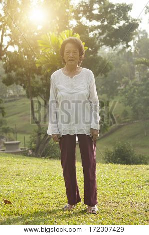 Portrait of healthy happy Asian senior woman walking at outdoor nature park, morning beautiful sunlight background.