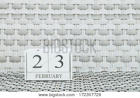 Closeup surface white wooden calendar with black 23 february word on blurred weave wood chair textured background with copy space in selective focus at the calendar