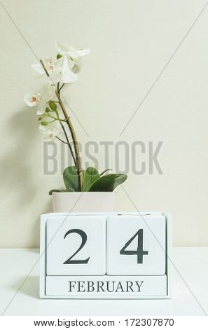 Closeup white wooden calendar with black 24 february word with white orchid flower on white wood desk and cream color wallpaper in room textured background in selective focus at the calendar