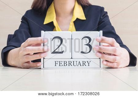 Closeup white wooden calendar with black 23 february word in blurred working woman hand on wood desk in office room in selective focus at the calendar