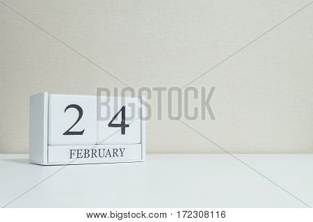 Closeup white wooden calendar with black 24 february word on blurred white wood desk and cream color wallpaper in room textured background with copy space in selective focus at the calendar