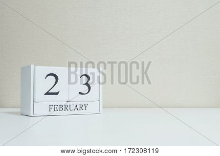 Closeup white wooden calendar with black 23 february word on blurred white wood desk and cream color wallpaper in room textured background with copy space in selective focus at the calendar
