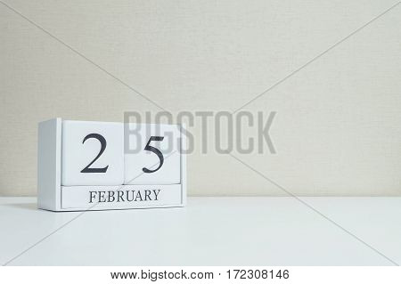 Closeup white wooden calendar with black 25 february word on blurred white wood desk and cream color wallpaper in room textured background with copy space in selective focus at the calendar