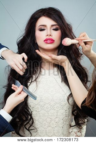 Professional Hair Stylist and Makeup Artist doing Make up and Hairstyle with Makeup Brush and Comb for Beautiful Woman. Beauty Makeup Concept