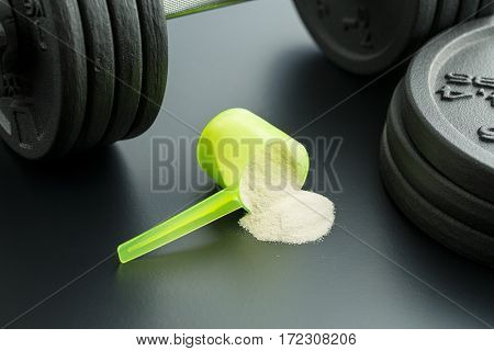 Whey protein powder and dumbbell.