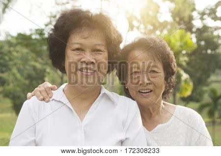 Portrait of healthy happy Asian seniors mother and daughter at outdoor nature park, morning beautiful sunlight background.